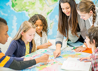 Teacher shares world map with students during social science class