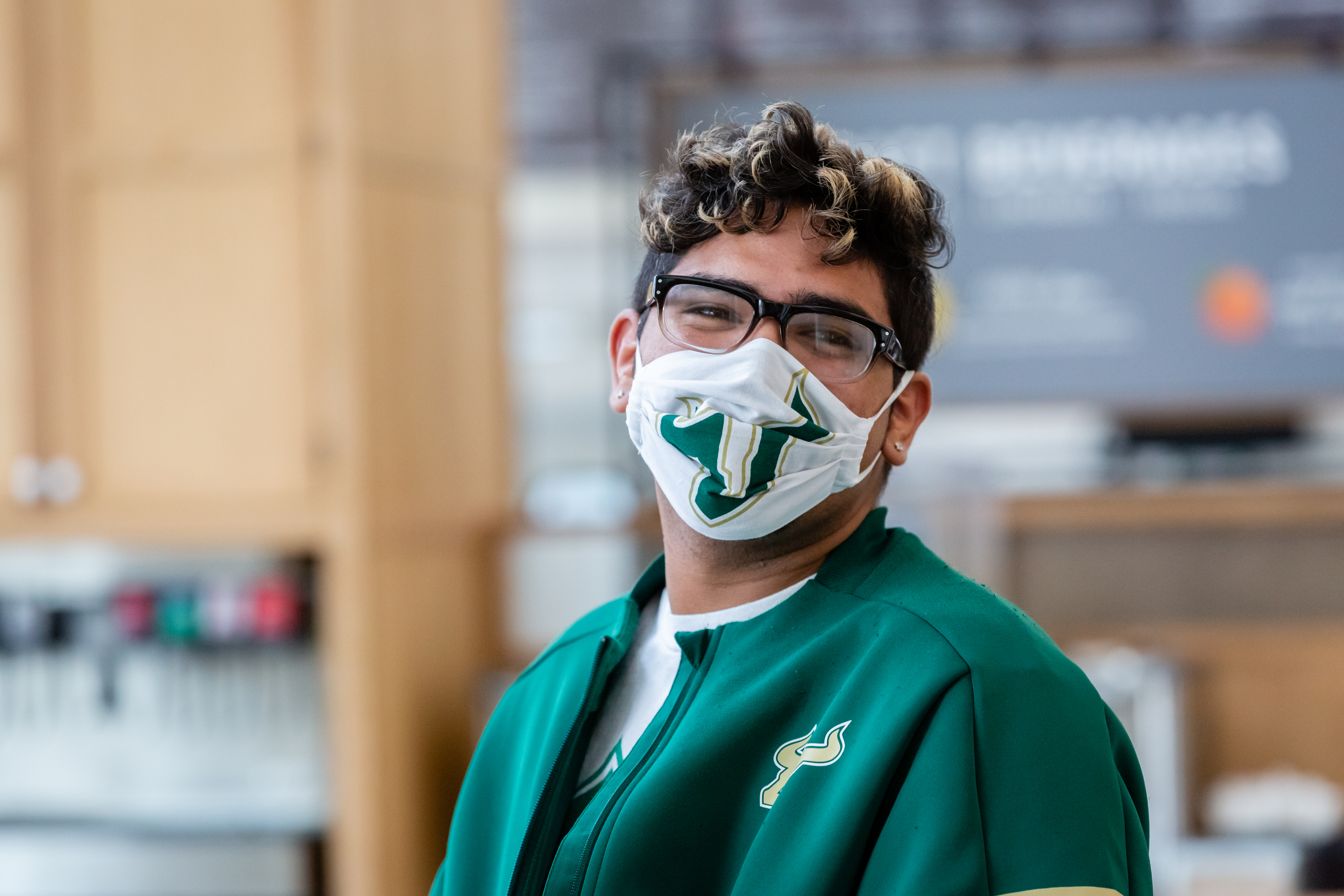Student in glasses smiling with Bull U mask on