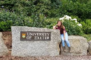 student sitting next to the University of Exeter welcome sign